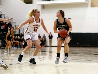 Madi Gaibler prepares to plant to shoot the basketball against a defender in the Gallogly Events Center