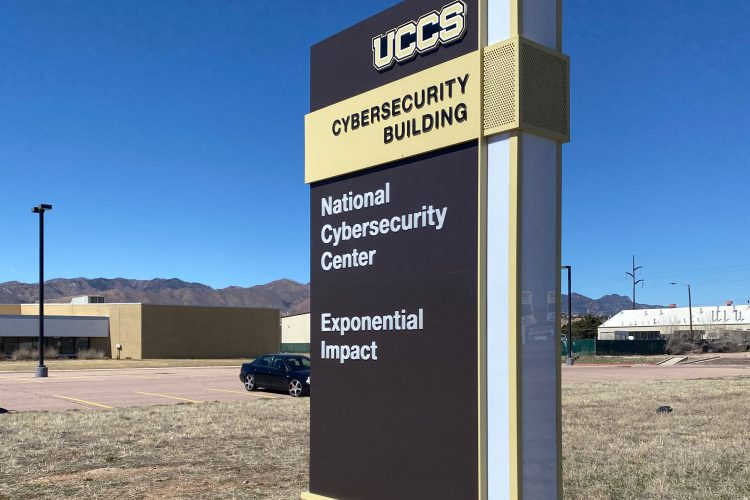 The exterior sign  at the UCCS Cybersecurity Building with a blue sky