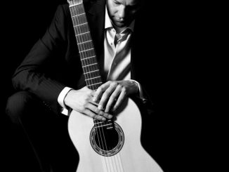 A black and white photo of Colin McAlister holding a guitar