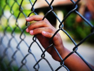 A hand rests on a chain link fence
