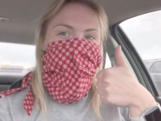 Michaela Norve gives a thumbs up sign while wearing a face mask in the car.