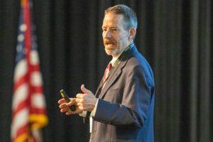 Chip Benight speaking at a conference with an American flag in the background