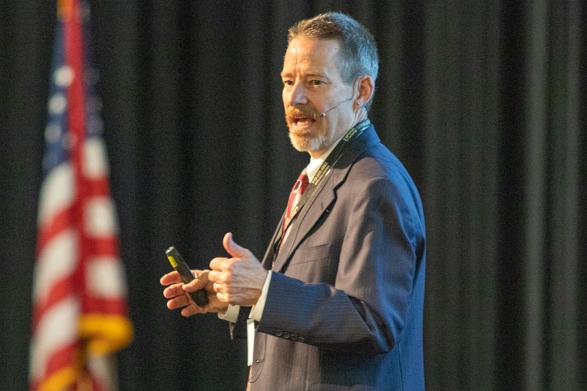 Chip Benight presents at a conference with an American flag in the background