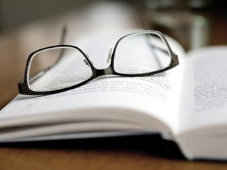 A pair of glasses laying on an open book page