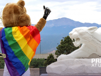Clyde with a rainbow flag standing next to the Mountain Lion statue