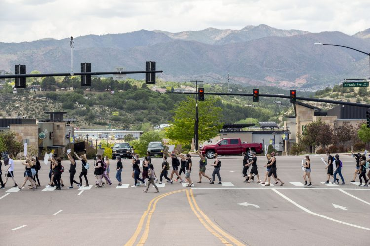 People walking across the street with mountain scenery in the background