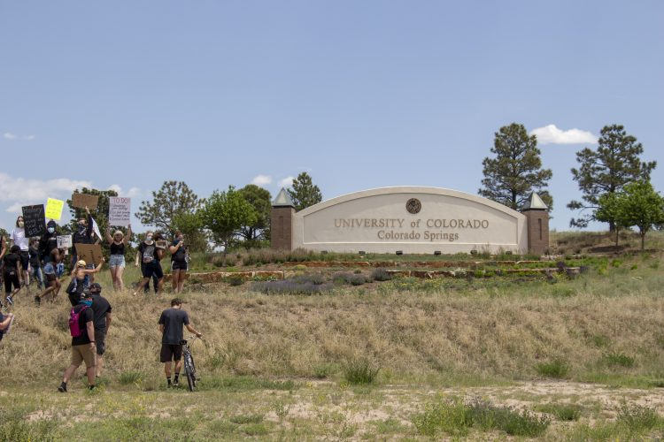 People gathering in front of the UCCS sign on the corner of Austin Bluffs and Nevada
