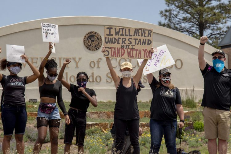 Students and staff protest in front of the UCCS sign