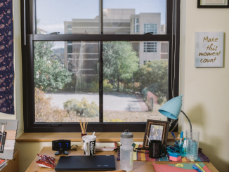 Picture of desk with a window looking at a building.