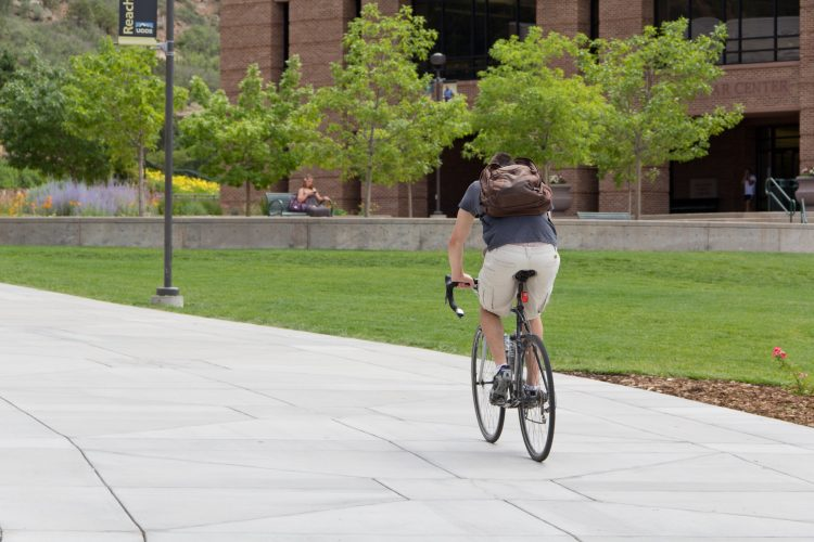 A student rides his bike on campus.