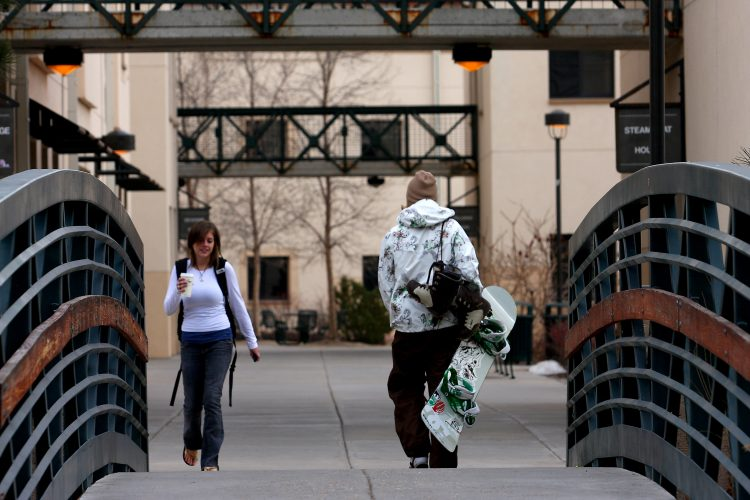 A student carries his snowboard through the Summit Village housing complex.