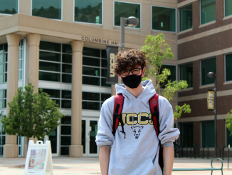Student wearing a mask standing in front of building
