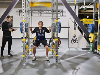 A person doing squats while a trainer looks on in the Hybl Sports Medicine and Performance Center