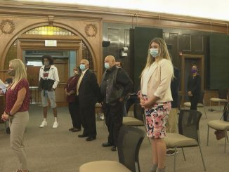 People standing in the city council chambers