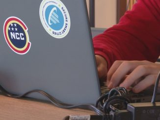 A student working on a laptop with a few stickers on the lid