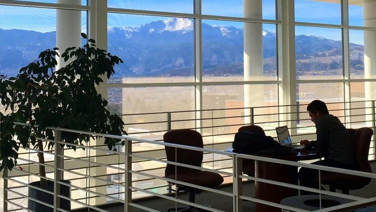 A student studying in Dwire Hall with Pikes Peak through the windows