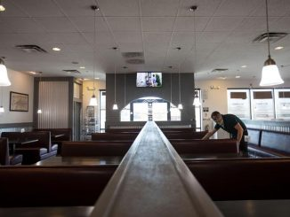 A person wipes down a table in an empty restaurant