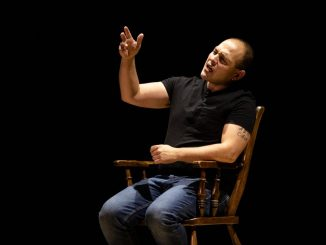 Jonathan Marcantoni performing a monologue from a chair