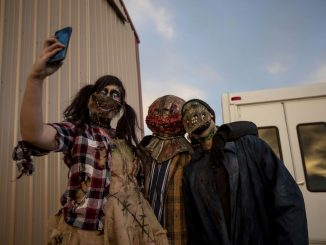 Three people take a selfie before performing at a haunted house