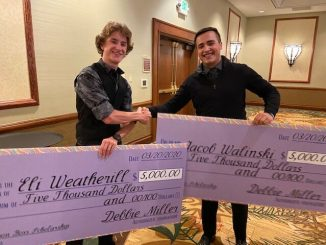 Eli Weatherill and Jacob Walkinski shaking hands after receiving a scholarship check
