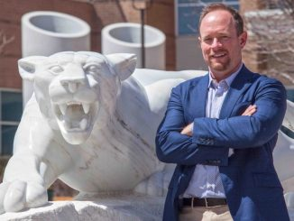 Craig Smith with his arms folder in front of the mountain lion statue
