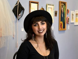 Jasmine Dillavou in front of a wall of artwork