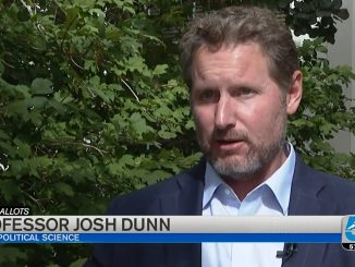 Josh Dunn conducting an interview in front of a tree