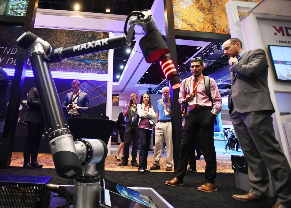 Two people look at a robot during the 2019 Space Symposium