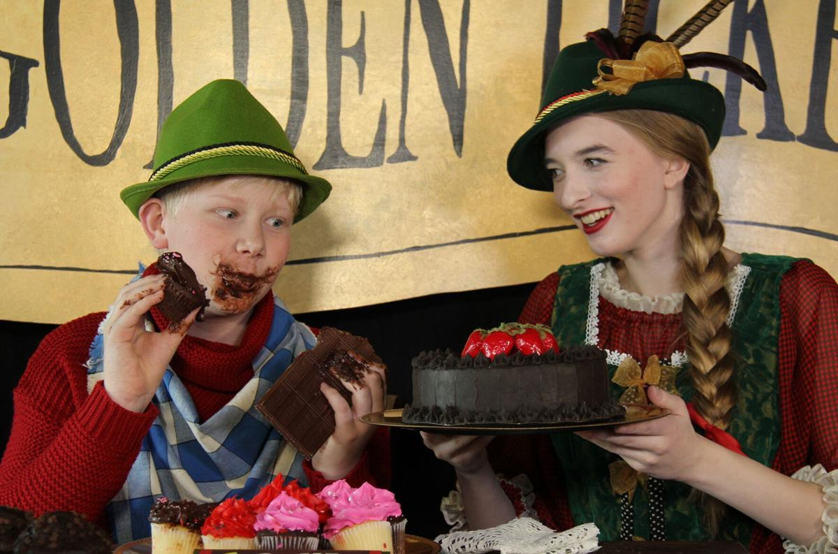 Two actors in a play, with one eating a chocolate cake with his hands