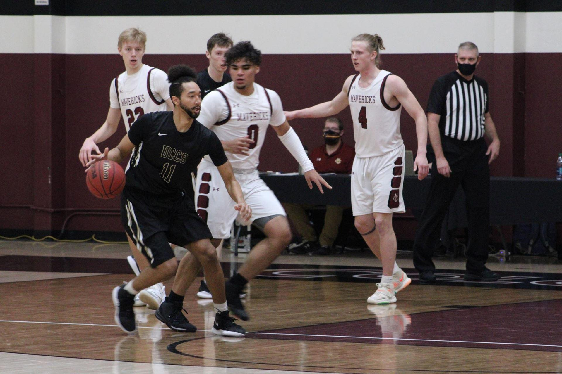 Geoff Kelly dribbling the basketball against Colorado Mesa defenders