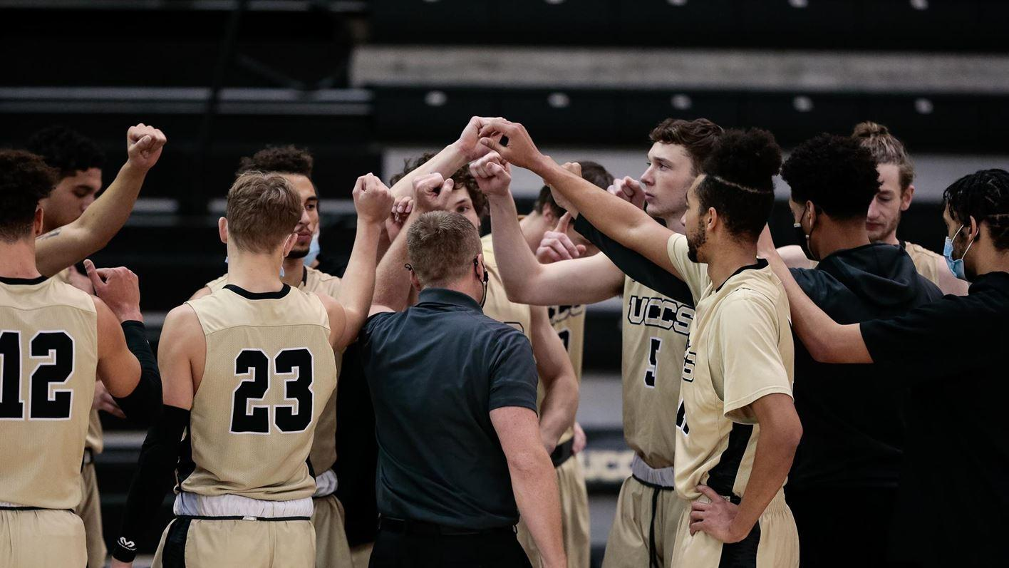 The UCCS men's basketball team with their arms up during a huddle