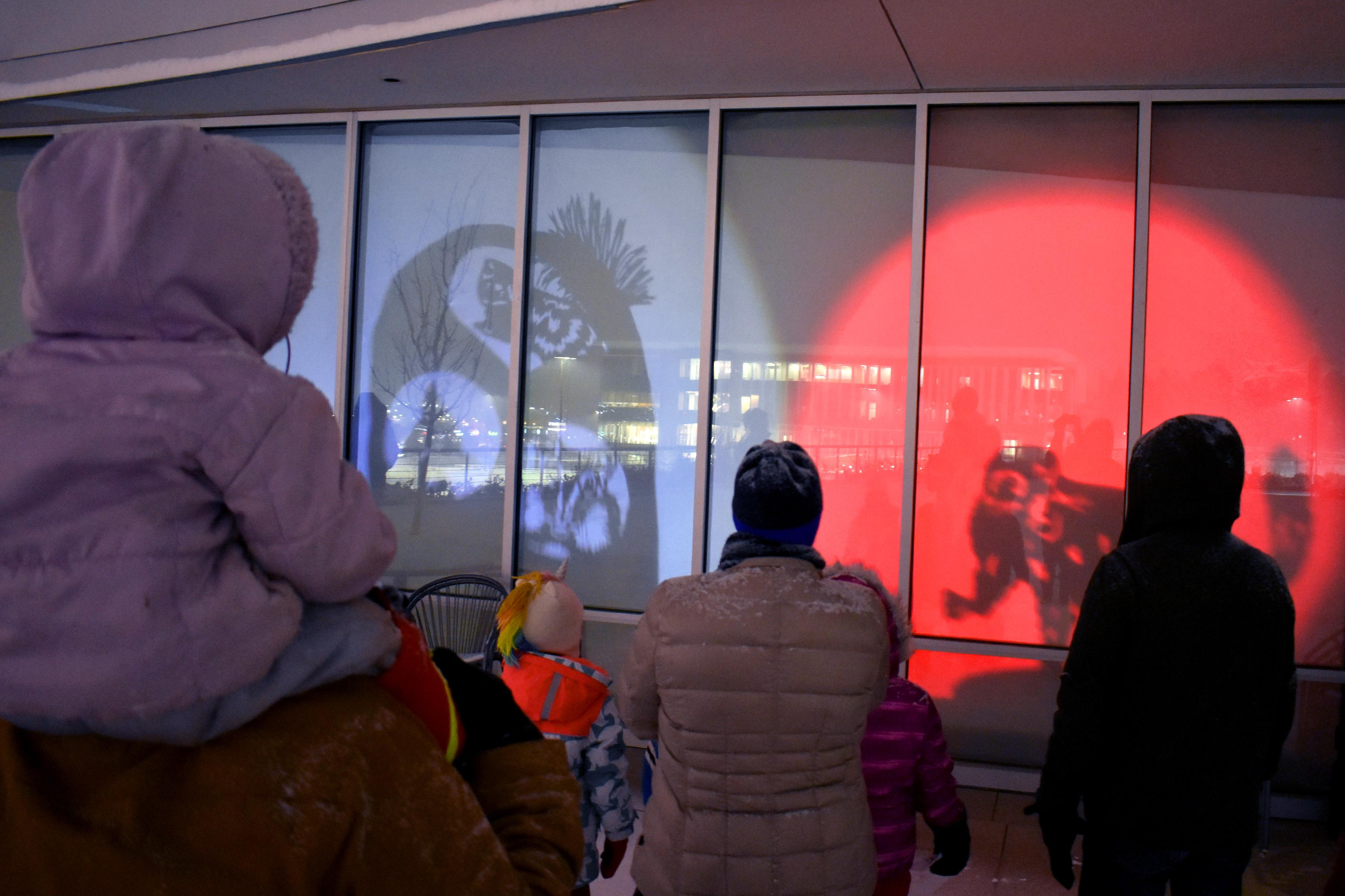 People watch as shadow puppets are displayed on the window.