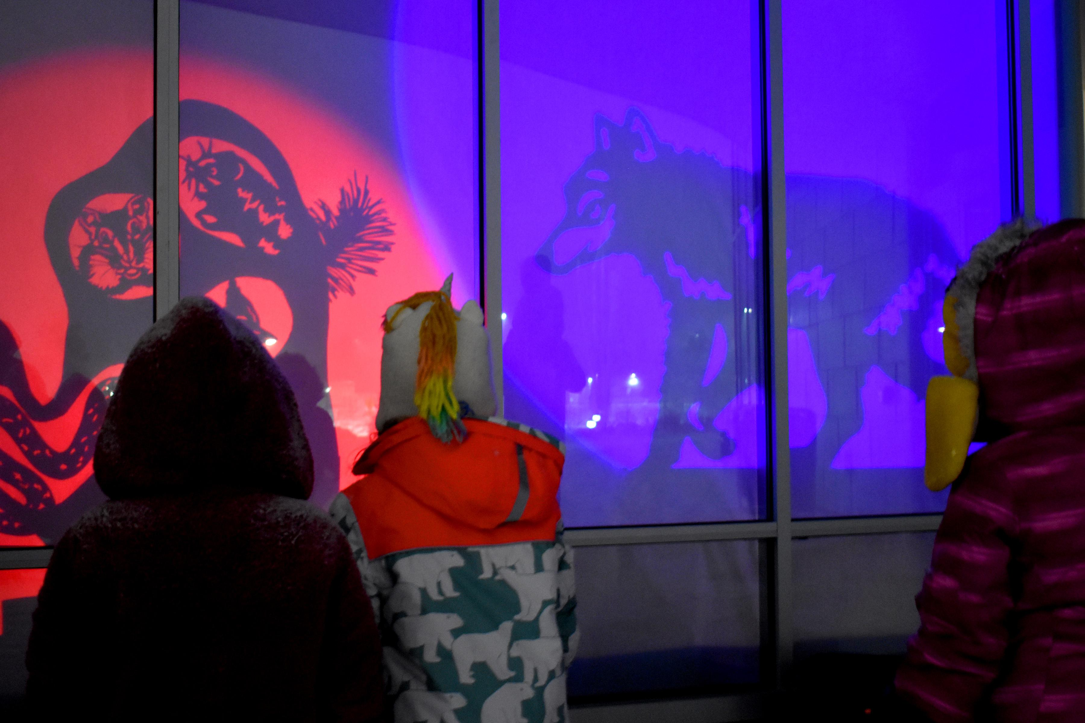 Shadow puppets displayed on a window with children looking at them