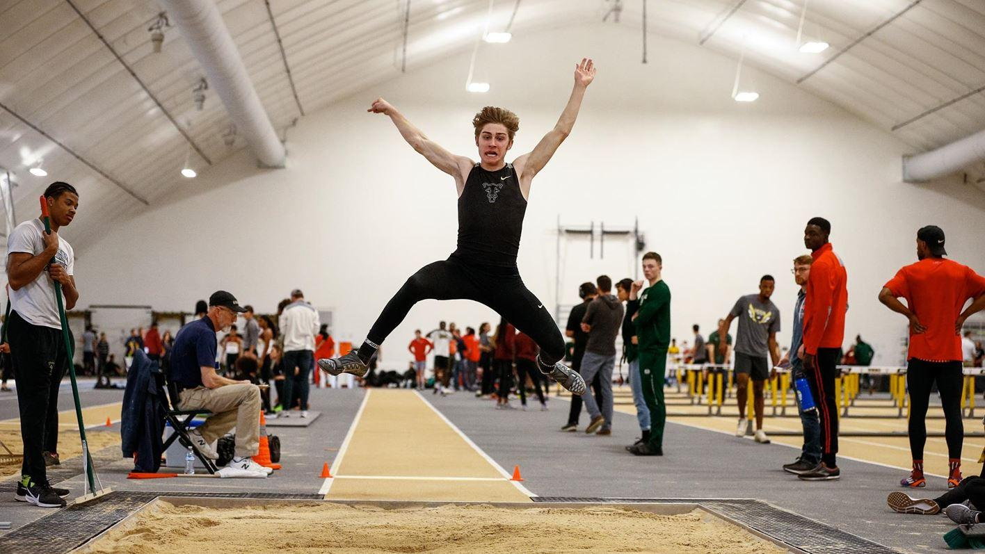 Peyton Turnage in midair during the long jump at Mountain Lion Fieldhouse