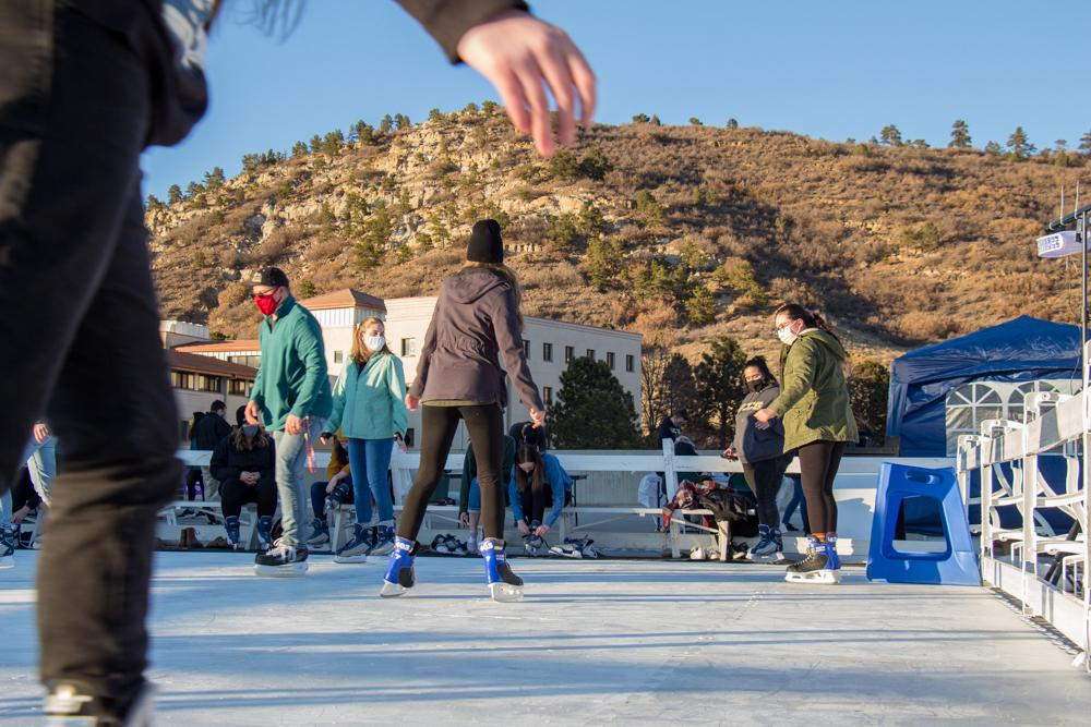 Students ice skate with a mountain in the backgrounf.