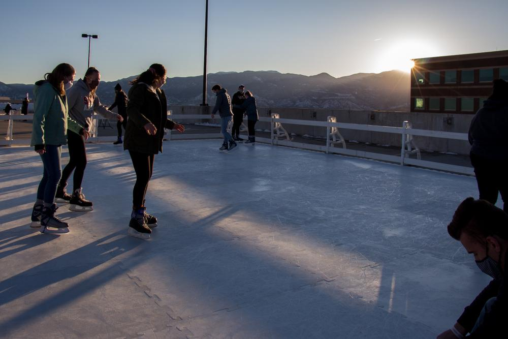 Students ice skate as the sun begins to go down