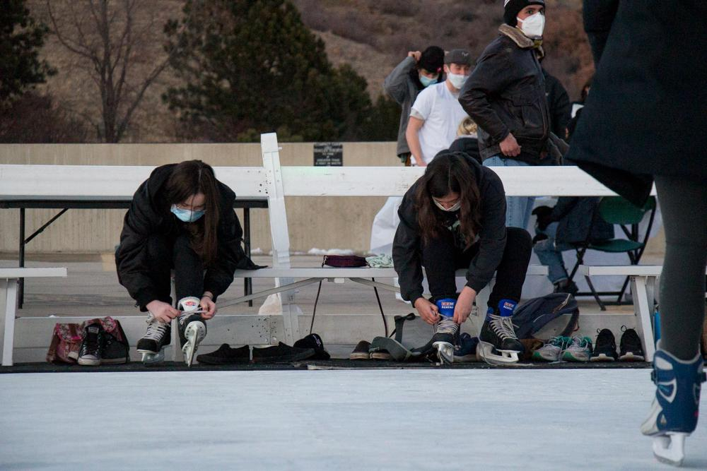 Two students lace their skates up