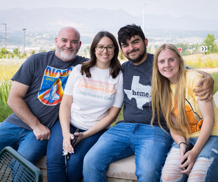 Four people pose for a picture together smiling