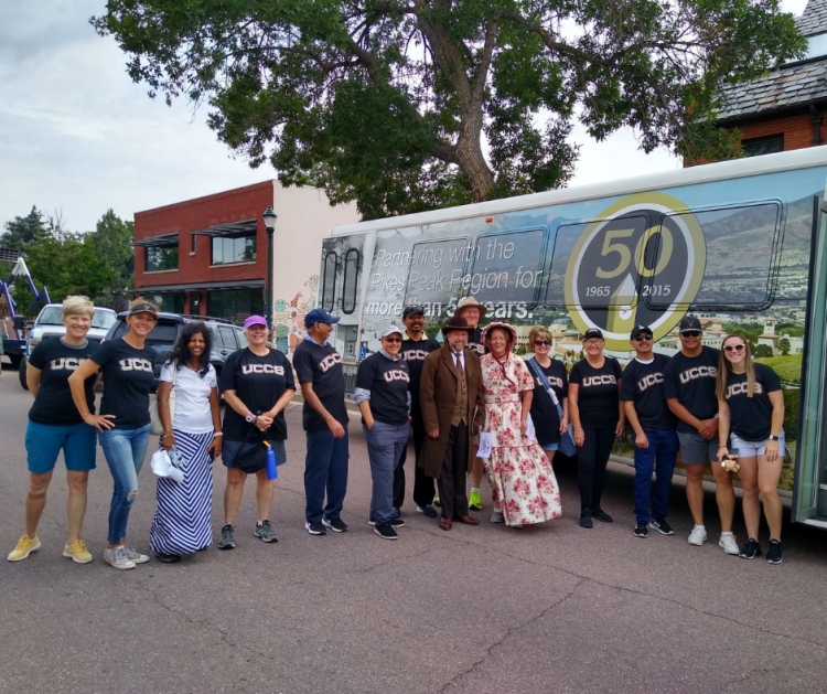 16 people stand shoulder to shoulder in front of the UCCS shuttle for a photo.
