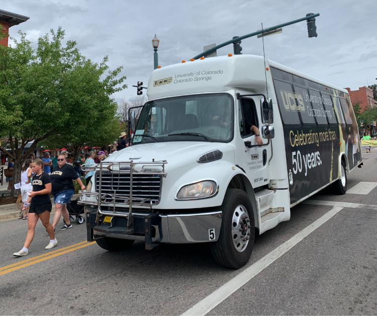 A UCCS shuttle drives in the downtown parade alongside members of the UCCS community.