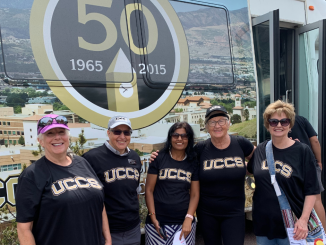 Five people wearing UCCS shirts pose in front of the UCCS shuttle.